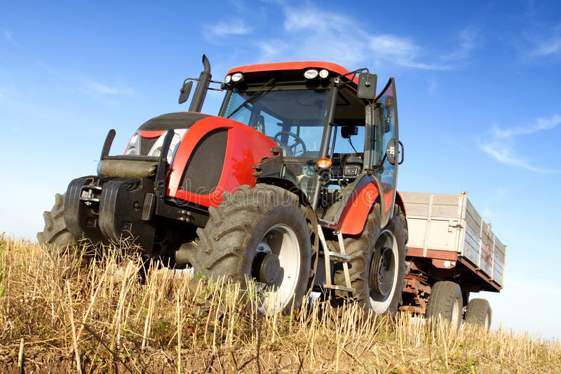 Agriculture. Tractor on the field with harvested corn stock photo