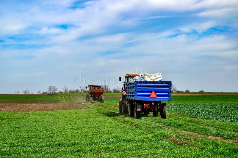 Tractor work on the field. Applying fertilizer in spring. Agriculture landscape. Two tractors on the road. One with equipment for spreading fertilizer, other royalty free stock photography