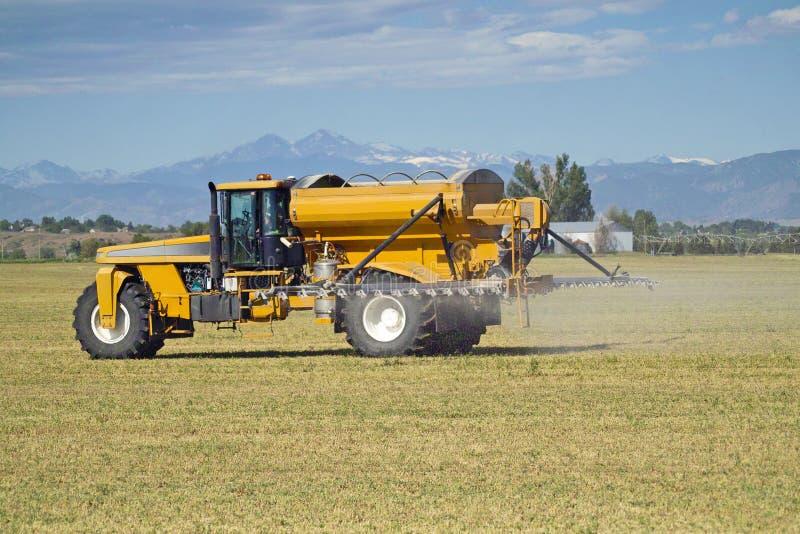 Agriculture machine spraying an alfalfa field stock photo