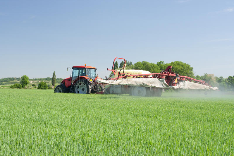 Agriculture - plant protection. Agriculture - tractor dusting chemical manure (plant protection with pesticides stock image