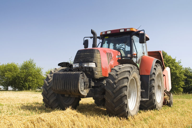 Agriculture - Tractor. Tractor on the field with straw royalty free stock photo