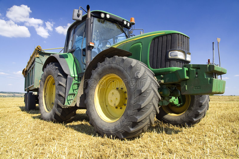 Agriculture - Tractor. On the field with harvested corn royalty free stock photography