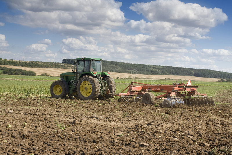 Agriculture - Tractor. With plough on the field stock photography