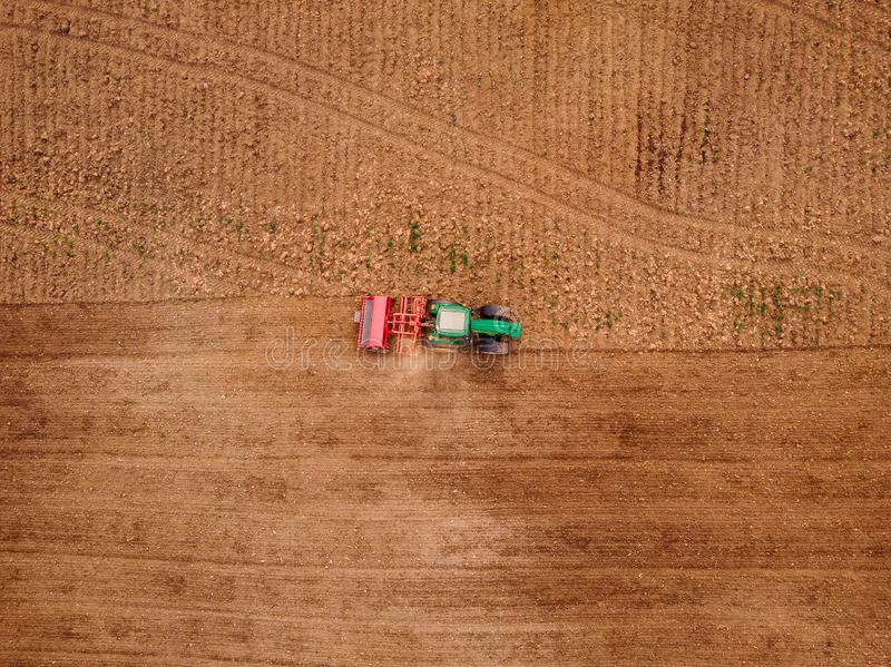 Agriculture tractor plows field of land for sowing. Top view aerial photo. Agriculture tractor plows field of land for sowing. Top view aerial photo stock photography