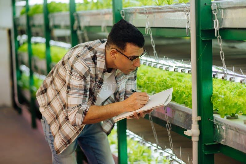 Agriculturist pisze notatkach w szklarni podczas gdy pracujący fotografia stock