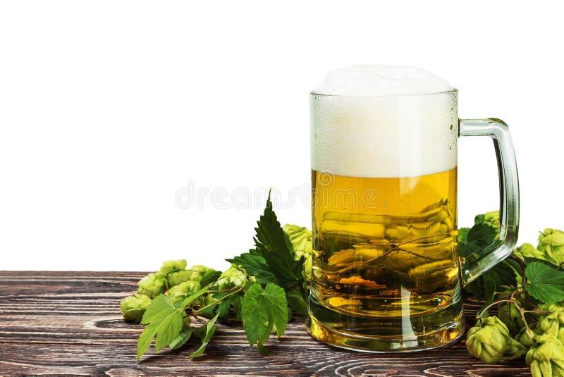 Agrida com cerveja com o lúpulo na tabela de madeira isolada imagem de stock royalty free