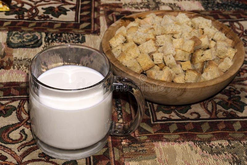 Agrida com uma bebida de leite ácido e uma bacia de madeira com biscoitos foto de stock royalty free