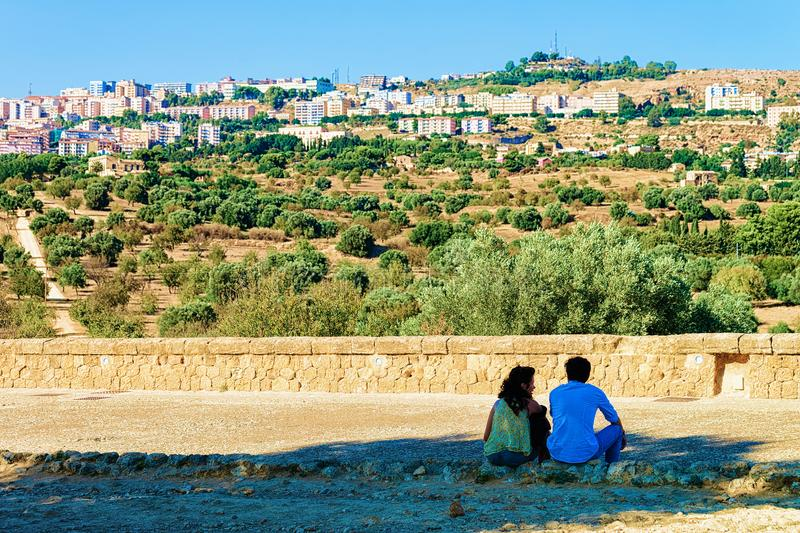 Agrigento, Italy - September 22, 2017: Young couple sitting in Agrigento with the landscape, Sicily, Italy. Agrigento, Italy - September 22, 2017: Young couple stock photo
