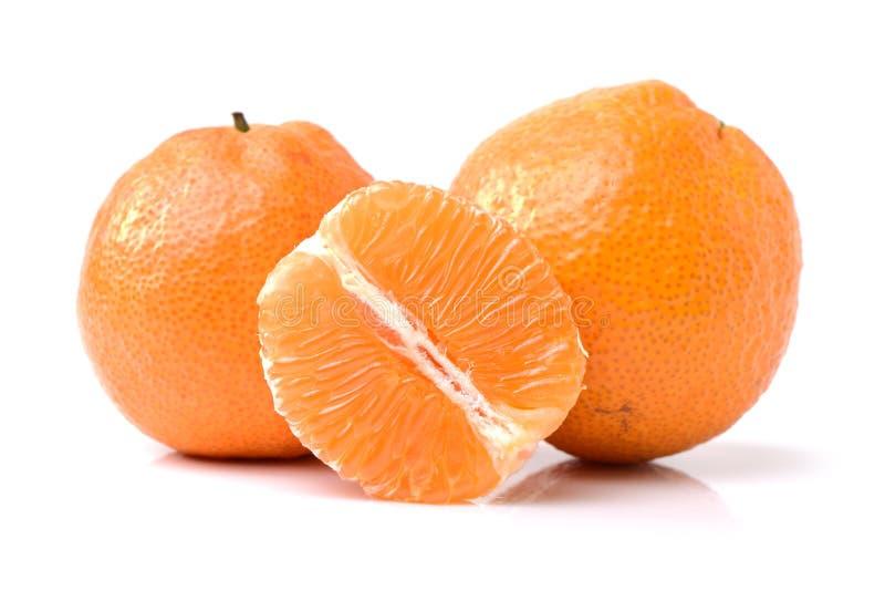 Agrios anaranjados sin pelar, pelados, partidos en dos y cortados imagenes de archivo