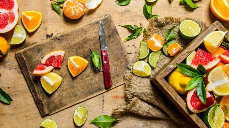 Agrios cortados - pomelo, naranja, mandarina, limón, cal en el viejo tablero con la caja foto de archivo