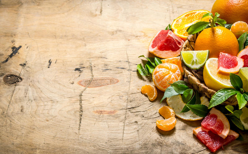 Agrios - pomelo, naranja, mandarina, limón, cal en una cesta con las hojas foto de archivo libre de regalías