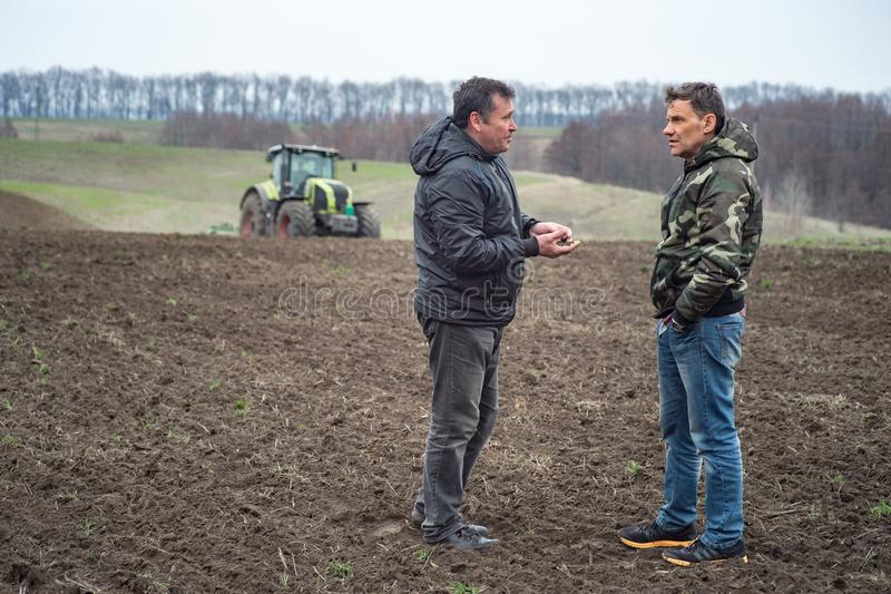 agronomist and farmer checks the soil moisture before sowing cereals stock image