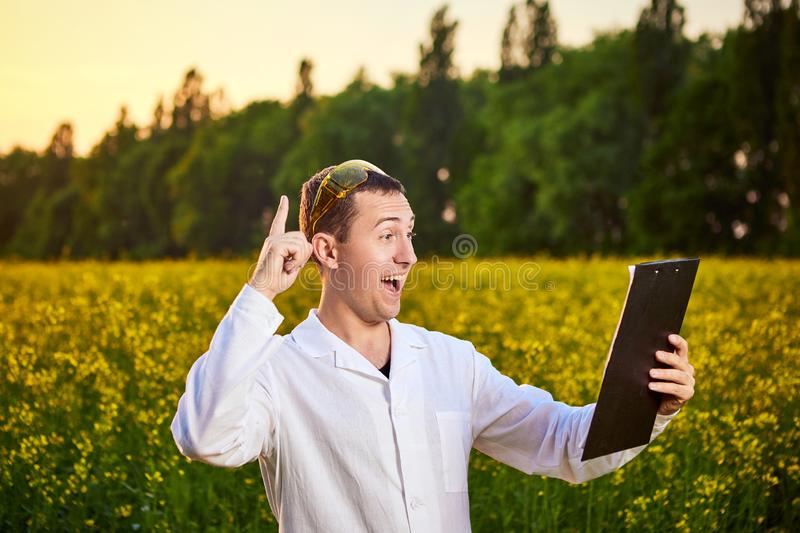 Agronomist man or farmer examine rapeseed oil using tablet on the background of  blossoming rape canola field. Agronomist man or farmer examine rapeseed oil royalty free stock photo