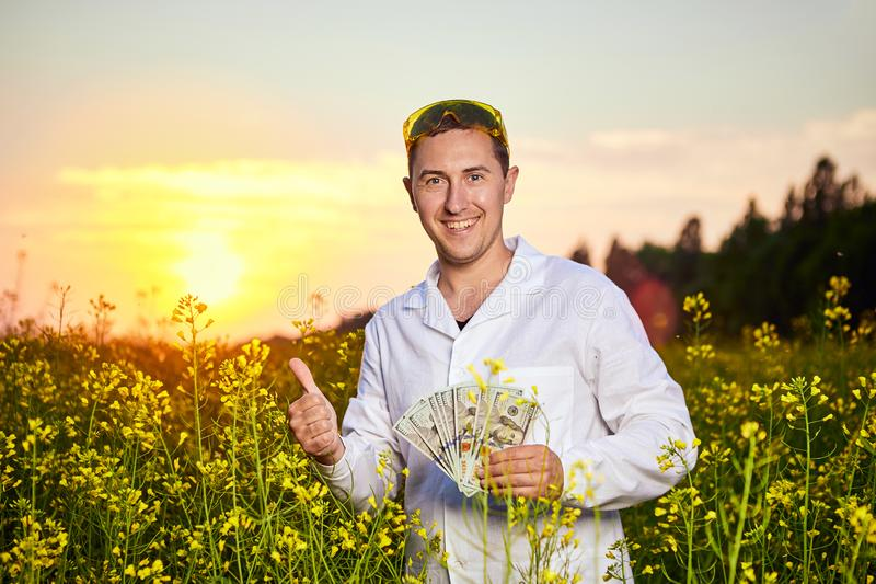 Agronomist man or farmer holding money dollar banknote with blossoming cultivated canola field in background. Agronomist man or farmer holding money dollar royalty free stock photo