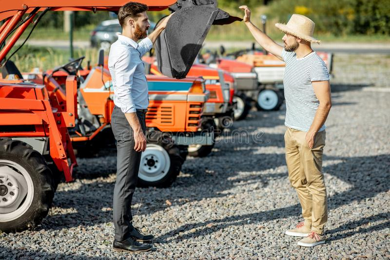 Agronomist with salesman near tractor at the agricultural shop. Agronomist choosing a tractor for farming, standing with salesman on the open ground of royalty free stock images