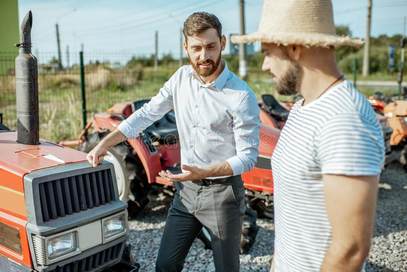 Agronomist with salesman near the tractor outdoors. Young agronomist with elegant salesman choosing a tractor for farming on the open ground of agricultural shop stock images