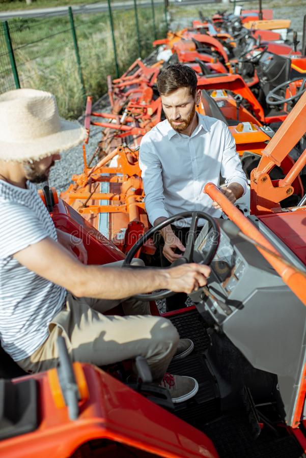 Agronomist with salesman near the tractor outdoors. Young agronomist with elegant salesman choosing a tractor for farming on the open ground of agricultural shop royalty free stock photos