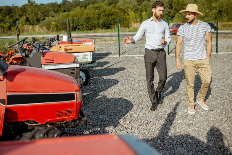 Agronomist with salesman near the tractor outdoors. Young agronomist with elegant salesman choosing a tractor for farming on the open ground of agricultural shop stock photos