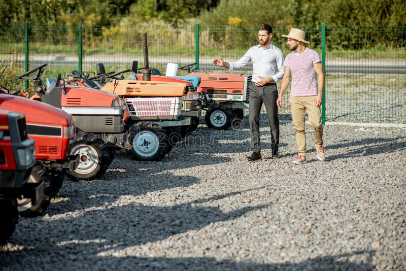 Agronomist with salesman near the tractor outdoors. Young agronomist with elegant salesman choosing a tractor for farming on the open ground of agricultural shop royalty free stock photo