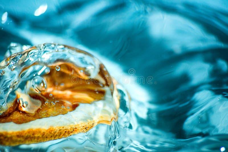 Agrume giallo in una spruzzata blu di acqua fotografia stock libera da diritti