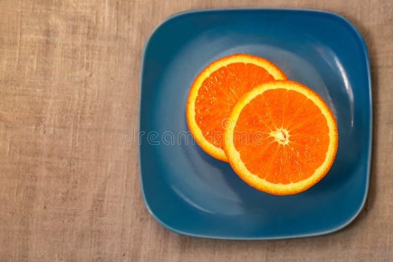 agrume Un mandarino è servito su un piatto blu fotografie stock