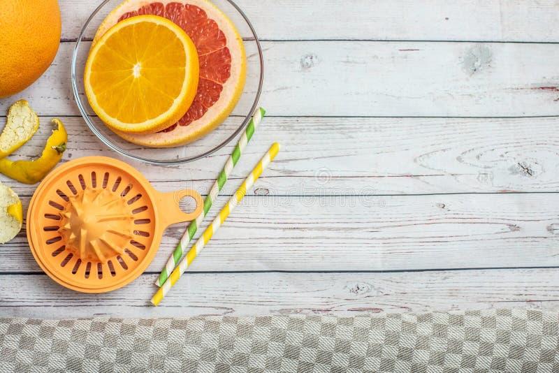Agrumes frais de tranches et presse-fruits manuel orange sur la table en bois légère Vue supérieure Avec l'espace de copie photographie stock