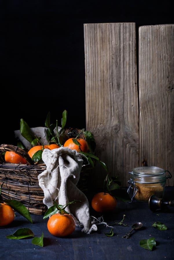 Agrumes oranges juteux mûrs dans un panier, sucre de canne dans une boîte, pour faire la confiture Fond foncé, foyer sélectif photos stock