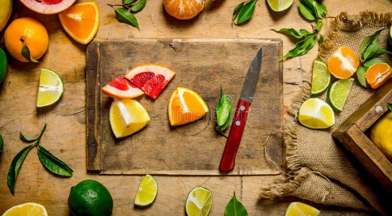 Agrumi affettati - pompelmo, arancia, mandarino, limone, calce sul bordo anziano con la scatola fotografie stock libere da diritti