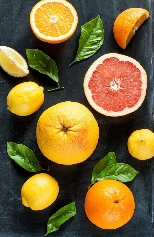 Agrumi (limone, pompelmo ed arancia) sulla lavagna nera immagini stock libere da diritti