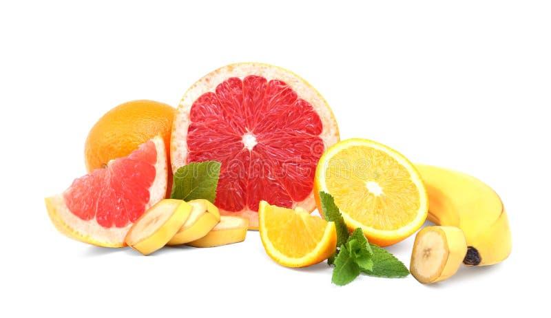 Agrumi naturali, organici, freschi: arancia, pompelmo e banana con le foglie verdi della menta isolate su un fondo bianco immagine stock