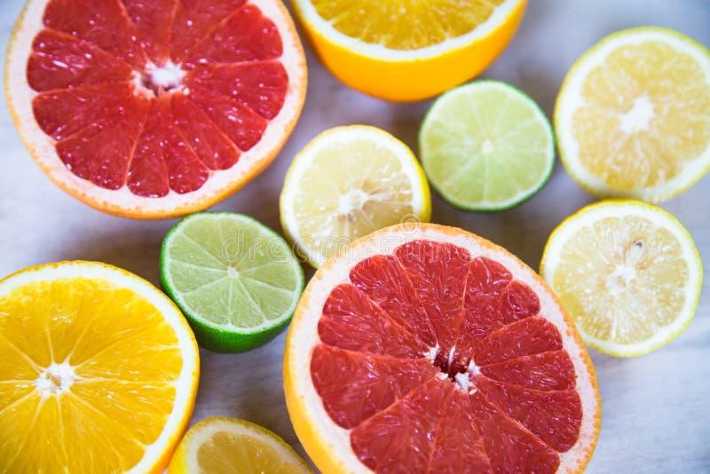 Agrumi pompelmo, arancia, limone, calce, sui precedenti di legno immagine stock