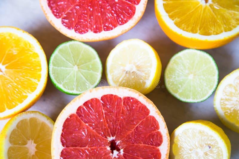 Agrumi pompelmo, arancia, limone, calce, sui precedenti di legno fotografia stock