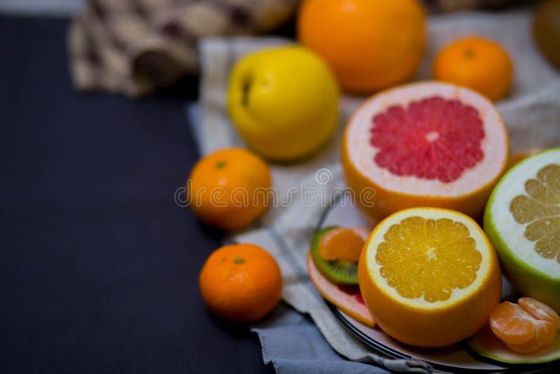 Agrumi succosi luminosi nel piatto ed asciugamano di cucina beige leggero marrone nella cucina, la tavola festiva fotografia stock libera da diritti