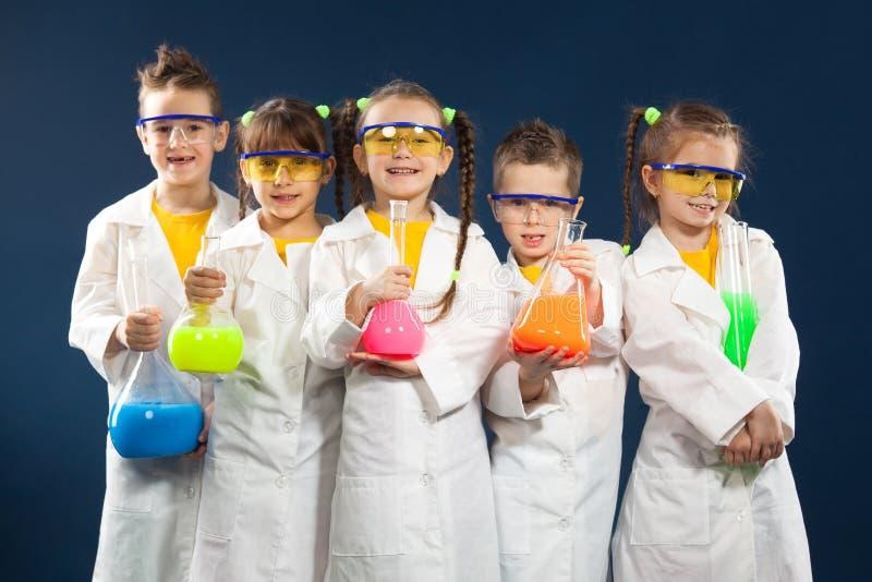 Agrupe as crianças felizes que fazem experiências da ciência no laboratório fotos de stock