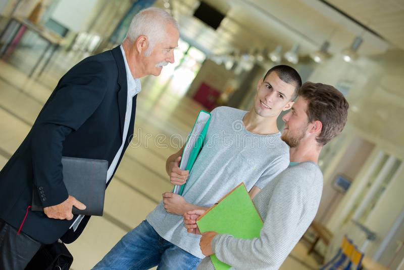 Agrupe as estudantes universitário que falam ao professor no salão da universidade foto de stock royalty free