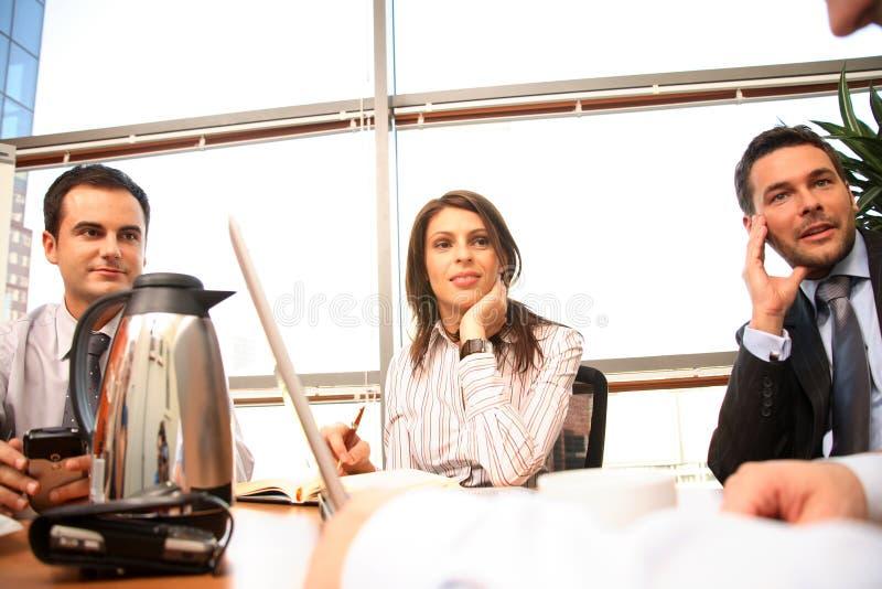 Agrupe as pessoas do negócio que trabalham junto com o portátil no escritório ensolarado imagem de stock royalty free