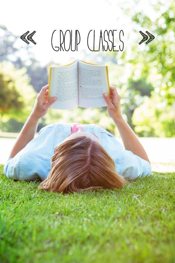 Agrupe classes contra o livro de leitura bonito da mulher no parque imagens de stock