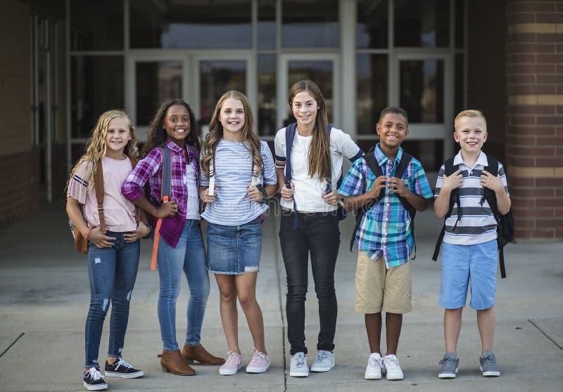 Agrupe el retrato de los niños preadolescentes de la escuela que sonríen delante de la construcción de escuelas foto de archivo libre de regalías