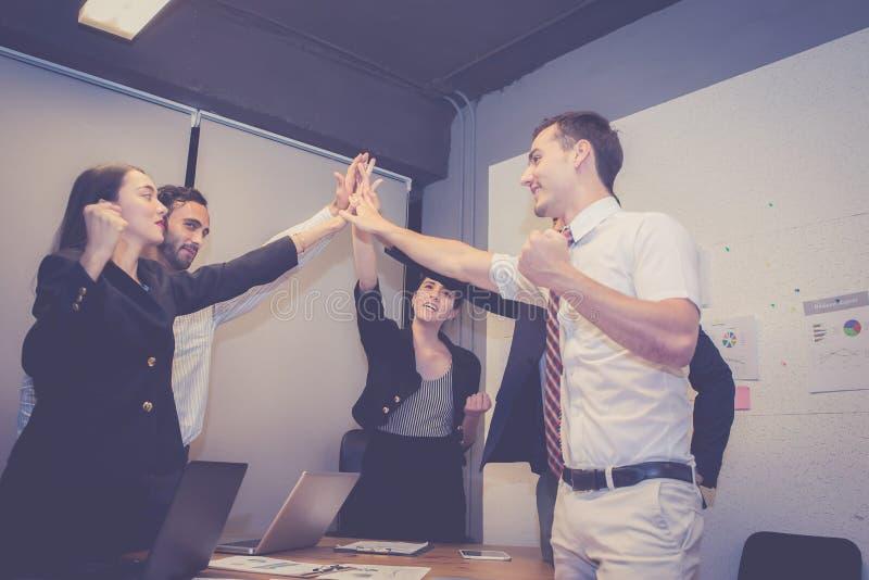 Agrupe a equipe asiática dos povos do negócio com o gesto do sucesso que dá olá! cinco na reunião, trabalhos de equipa do trabalh imagens de stock