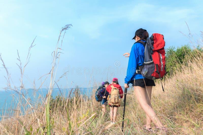 Agrupe jovens mulheres asiáticas dos caminhantes que andam com trouxa em um céu azul da montanha imagem de stock royalty free
