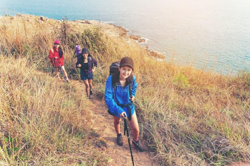 Agrupe a las mujeres jovenes de los caminantes que caminan con la mochila en una montaña en la puesta del sol El acampar que va d foto de archivo libre de regalías