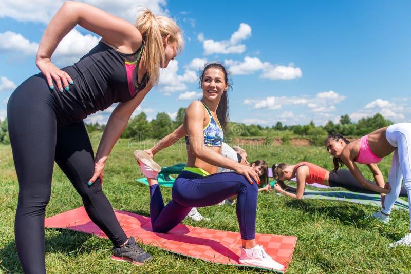 Agrupe a las mujeres que calientan antes de estirar de entrenamiento, ejercitando al aire libre imagenes de archivo