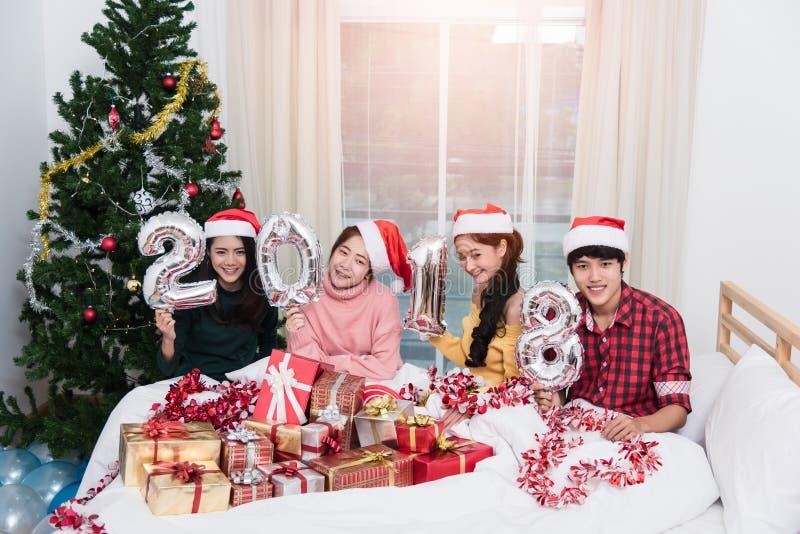 Agrupe a los amigos que celebran la Navidad en casa y que muestran 2018 para arriba foto de archivo libre de regalías