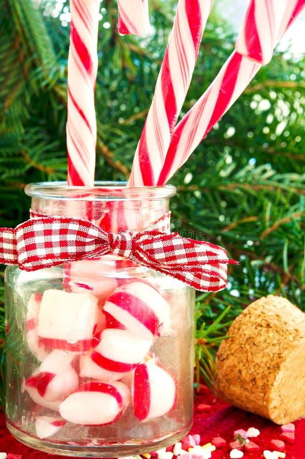 Agrupe los bastones de caramelo rayados en el tarro de cristal en fondo de la Navidad imágenes de archivo libres de regalías