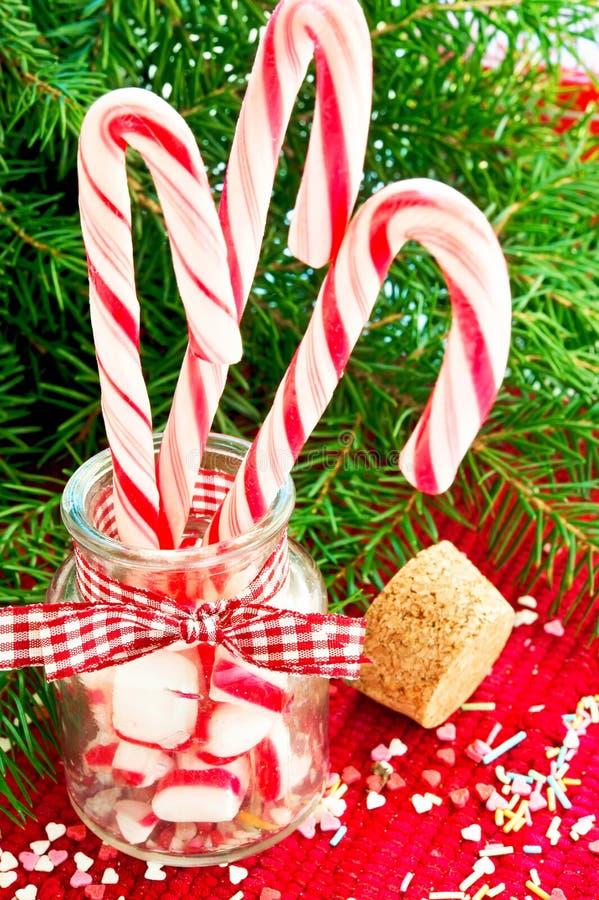 Agrupe los bastones de caramelo rayados en el tarro de cristal en fondo de la Navidad fotografía de archivo libre de regalías