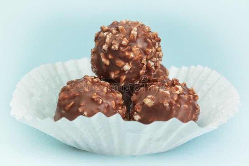 Agrupe los caramelos de chocolate en una cesta del Libro Blanco. imagenes de archivo