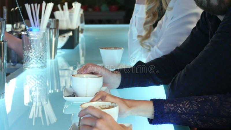 Agrupe a los hombres de negocios que charlan y que beben el café en una barra imagenes de archivo