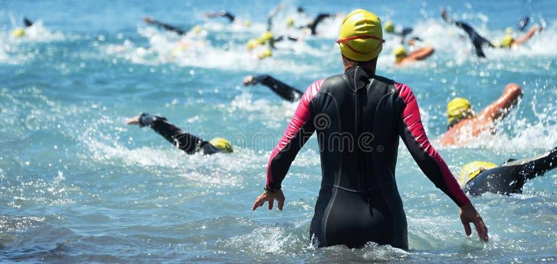 Agrupe a los participantes del triathlon que corren en el agua para la nadada fotos de archivo libres de regalías