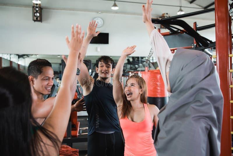 Agrupe o hijab dos povos e das mulheres que faz a elevação cinco no gym imagem de stock royalty free