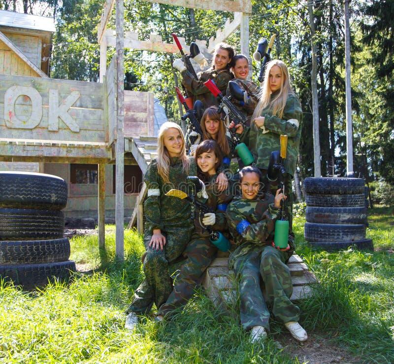Agrupe o retrato dos modelos fêmeas que levantam no uniforme militar fotografia de stock